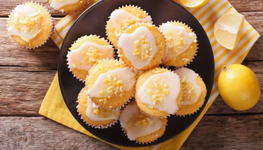 Sweet lemon muffins with zest and icing sugar close-up on a plate. horizontal top view
