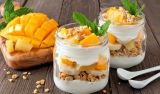 Mango, pineapple parfaits in mason jars on rustic wood