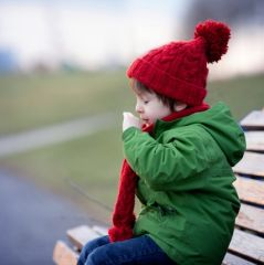 Little boy, sneezing and blowing his nose outdoor