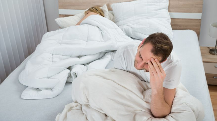 Depressed Man On Bed While Woman Sleeping