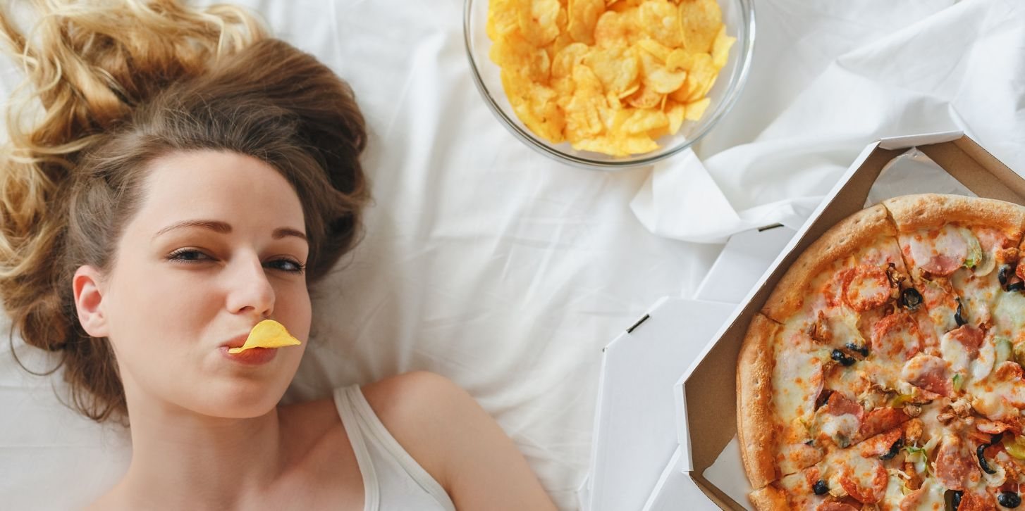 Girl eating chips on the bed, standing next to pizza